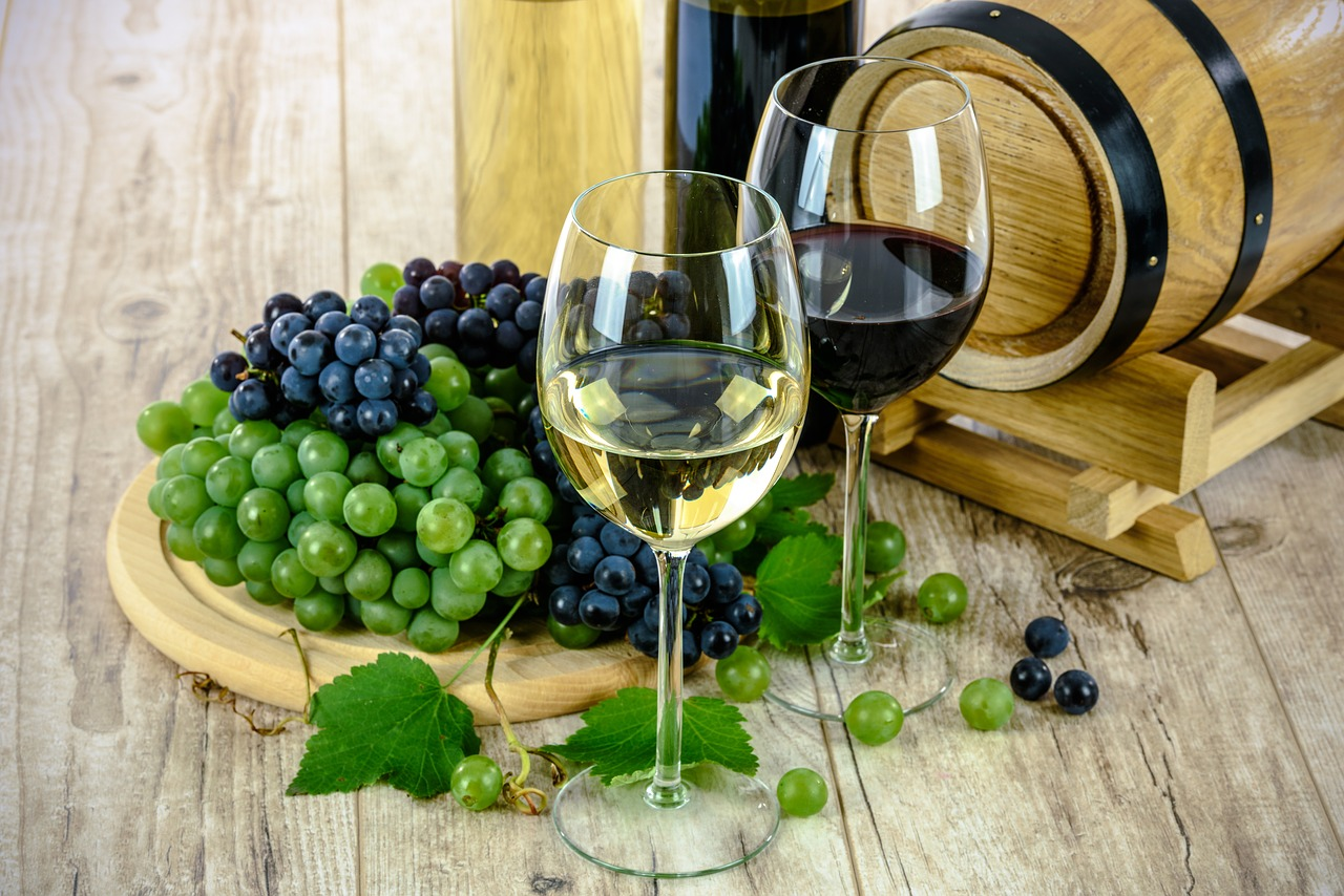 Two glasses of wine, one red and one white, on a wooden table with grapes.